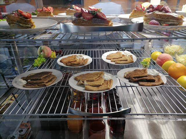Десерты и блинчики на витрине столовой